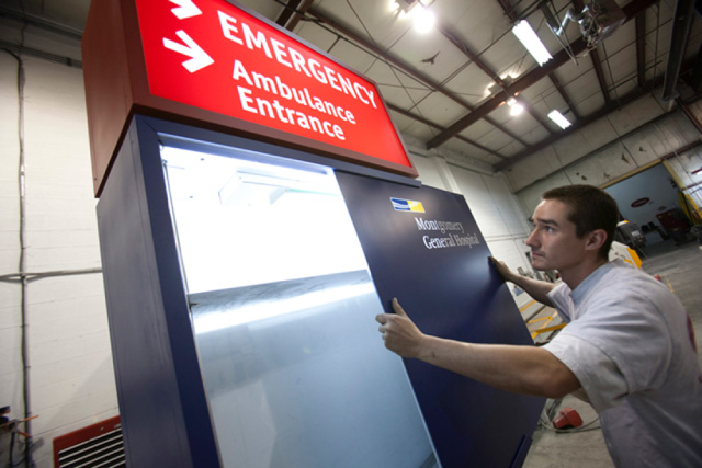 Apple team member installing hospital emergency sign
